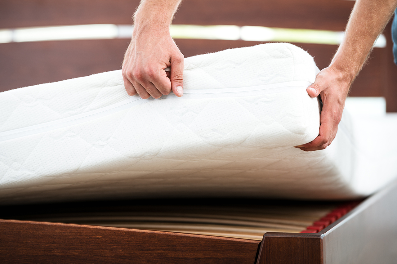 Hands pulling a mattress away from a bed frame